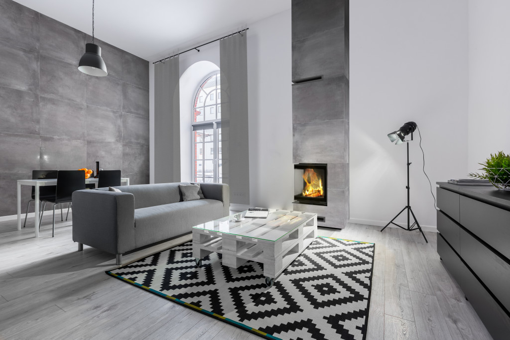 Gray and white loft apartment with sofa, pallet table, carpet and studio lamp